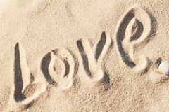 Love, word - written by hand in sand on a sea beach Royalty Free Stock Images