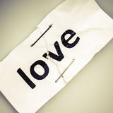 Love word written on torn and stapled paper Royalty Free Stock Photo