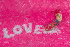 Love wording arrange by bead with thread bead in condom. On pink mulberry paper background Royalty Free Stock Photos