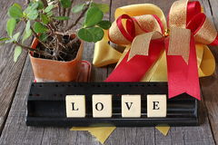 Love wording by crossword on old wooden board with ribbon and tree in pod background Royalty Free Stock Photography