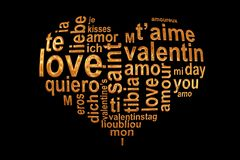 Love words in a golden heart on black background, Valentine multilingual wordcloud greeting card royalty free stock image