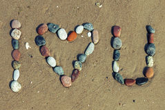 Love words written on the beach. Phrase I love you made of pebble stones on the sandy beach Royalty Free Stock Images