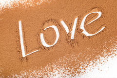Love written in Cocoa scattered Royalty Free Stock Photos