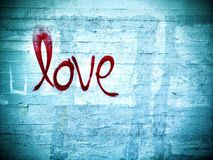 Love. Written on a concrete wall in red spray paint Stock Images