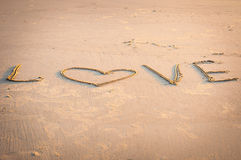 LOVE is written by hand in sand Stock Photography