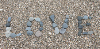 Love written in pebbles on a beach Stock Photography
