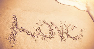 Love written on sand with waves Stock Images
