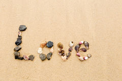 Love written in seashells in sand Royalty Free Stock Image