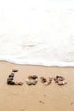 Love written in seashells in sand Stock Images