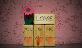 Love  written on wood blocks. Words written on wood blocks on table with pink background. Valentines day and love concept. Flower on wooden blocks. Template for Stock Images