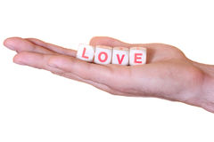 Love written with wooden dice on a hand, isolated on white background Royalty Free Stock Photo