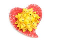 Love - yellow bow on red heart. Over white background Royalty Free Stock Photos