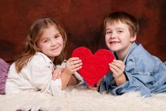 We love you. Happy kids holding a red heart Stock Photo