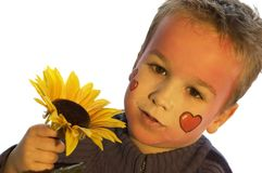 Love You. Lovely boy with painted heart face giving you a flower. Use it for valentine designs or just as a love picture royalty free stock photos