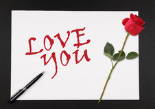 Love You. A piece of paper with a stalk of rose and pen, and the words Love You Royalty Free Stock Photos