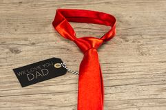 We love you dad. Close up of blank tag on orange necktie writing we love you dad Royalty Free Stock Photography