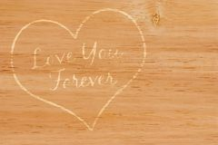 Love You Forever. Heart engraved in wood royalty free stock photos