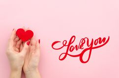 Love You hand lettering. woman hans holds red heart on a pink background Top view flat lay trendy. Love You hand lettering. woman hans holds red heart on a pink stock photo