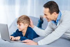 Loving father patting head of his son using laptop. Love you. Happy middle-aged men lying on the bed next to his son and patting his head gently while the boy Royalty Free Stock Photography