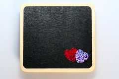 Love you. 2 hearts on mini wooden blackboard. Room for customised text Stock Photo