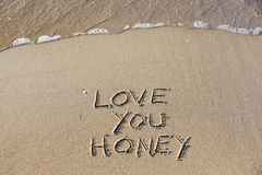 Love you honey written on the beach. Stock Photography