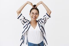 Love you. Indoor shot of happy and funny cute woman in glasses and bun hairstyle, raising hands above head, forming royalty free stock images