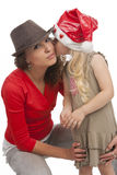 Love you kiss me!. Young caucasian happy looking mother in hat together with her daughter kissing and embracing. sitting on hunkers and isolated over  white Royalty Free Stock Photography
