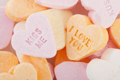 Love you and kiss me candy hearts. Many candy hearts with text and love you Stock Photos
