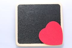 Love you. Large red heart on black board background. Room for customised text Stock Photos