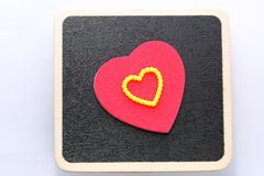Love you. Large red heart with yellow heart on black board background. Room for customised text Stock Image