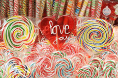 Love you lollipop III. Heart shaped lollipop with love you words in the center, and two more lollipops on each side and colored lollipops in the background royalty free stock photos
