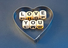 Love you. Message' Love you ' in black upper case letters on small white  cubes inside a silver heart shape  on gray background Stock Images