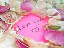 Love you message on pink sticky note with dry rose and orchid flower petals and jewelry ring and chain on wooden background royalty free stock photos