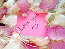 Love you message on pink sticky note with dry rose and orchid flower petals and silver jewelry ring and chain on wooden back royalty free stock image