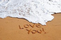 Love you. Message in the sand with wave approaching Royalty Free Stock Photography