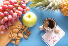 Love you note and healthy breakfast. Blue wooden table full with fresh fruits, grapes, pineapple, apple, almonds and walnuts, a cup of coffee and a love you note Stock Image