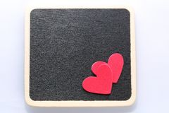 Love you. 2 red hearts on black board background. Room for customised text Stock Image
