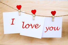 Love you text on stickers hanging on heart shape pins. Love you text written at paper stickers hanging on red heart shape wooden pins and pack-thread at wooden Royalty Free Stock Photo