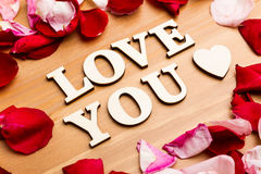 Love You wooden letters with rose petal besides Royalty Free Stock Photo