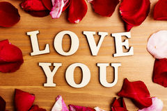 Love you wooden text and rose petal Royalty Free Stock Photos