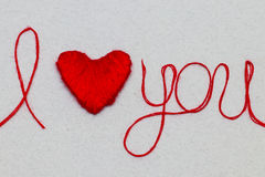 Love you words and heart symbol made of red thread on a white fo Stock Images