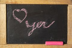 Love you written on blackboard with pink chalk stock photography