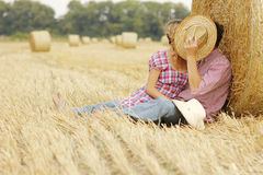 In love young couple on haystacks in cowboy hats. A in love young couple on haystacks in cowboy hats royalty free stock images