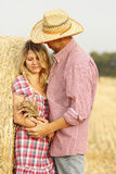 In love young couple on haystacks in cowboy hats Royalty Free Stock Photos