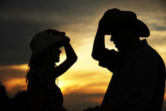 In love young couple on haystacks in cowboy hats Stock Photography