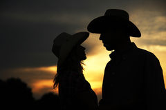 In love young couple on haystacks in cowboy hats Stock Images