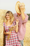 In love young couple on haystacks in cowboy hats Stock Photo