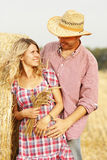 In love young couple on haystacks in cowboy hats Royalty Free Stock Photography