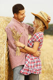 In love young couple on haystacks in cowboy hats Royalty Free Stock Image