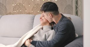 Love, young couple hug on sofa in home. Love, relationship, young couple hug on a cozy sofa in home room and kiss stock footage